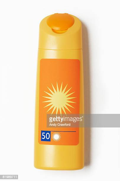 yellow bottle of sun cream - sunscreen stock photos and pictures