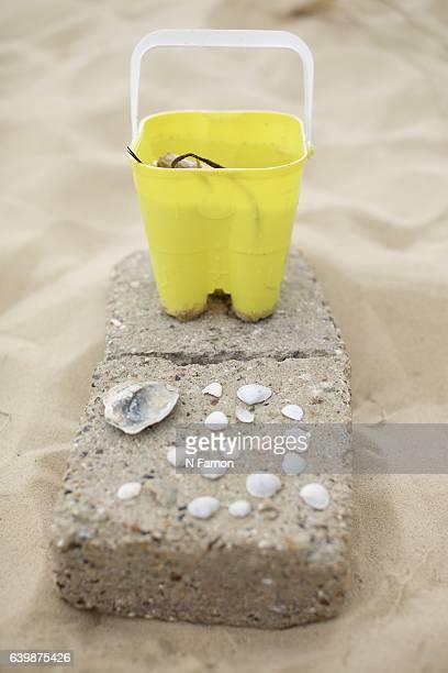 Yellow bucket on sand with shells
