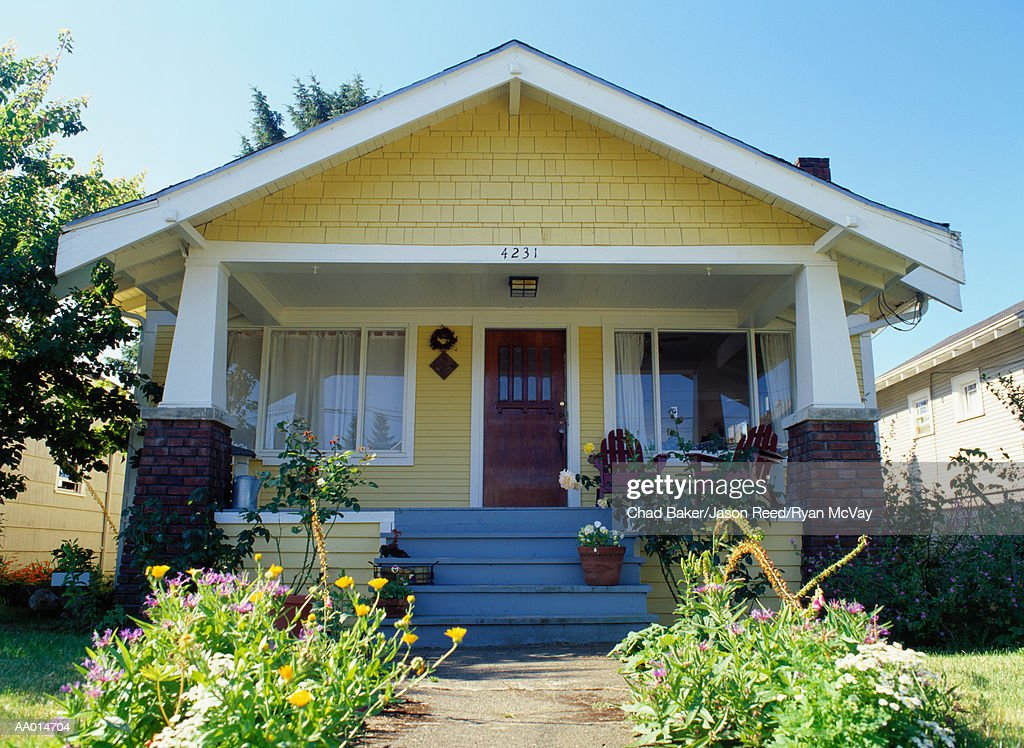 yellow bungalow style house with garden exterior view
