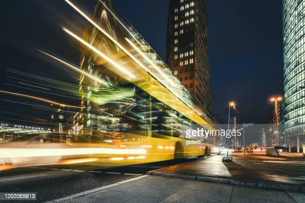 yellow bus on potsdamer platz at blue hour - sony center berlin stock pictures, royalty-free photos & images