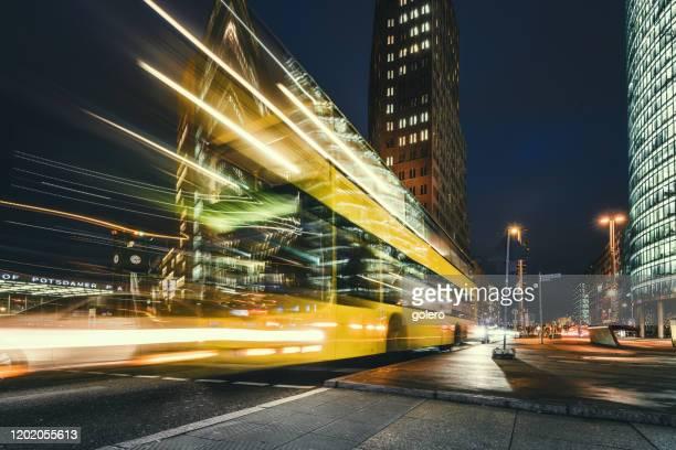 gelber bus am potsdamer platz zur blauen stunde - bus stock-fotos und bilder