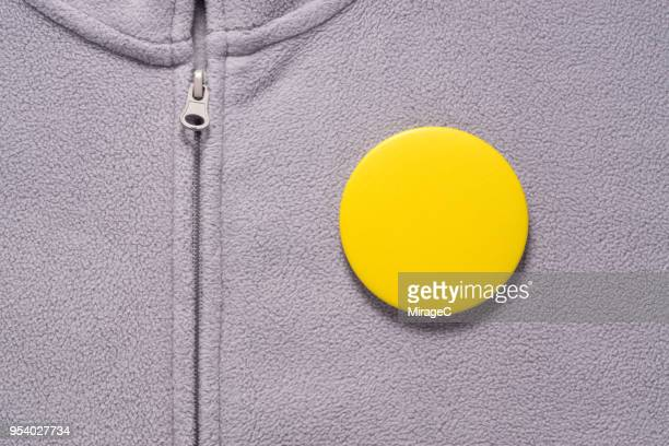 yellow button badge on gray cloth - brooch stock pictures, royalty-free photos & images