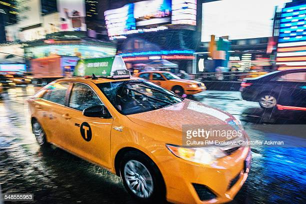Yellow cab and neon signs in Times Square at night, New York, USA