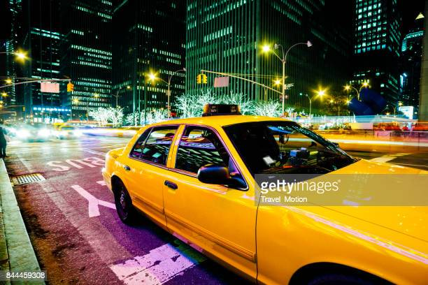 yellow cab at night in midtown manhattan, new york city - yellow taxi stock pictures, royalty-free photos & images