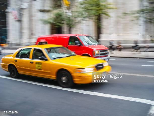yellow cab on street - イエローキャブ ストックフォトと画像