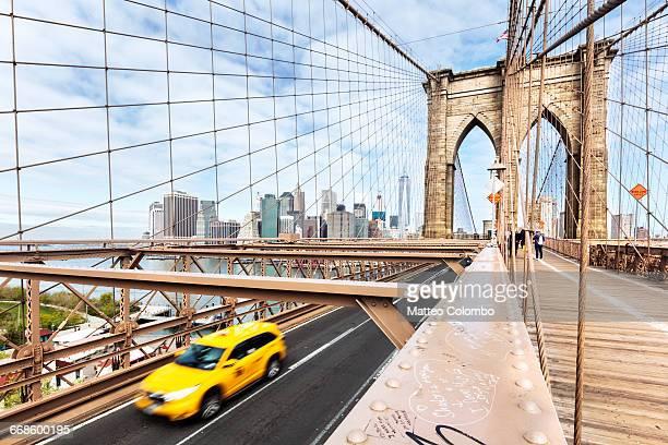 Yellow cab passing on Brooklyn bridge, New York