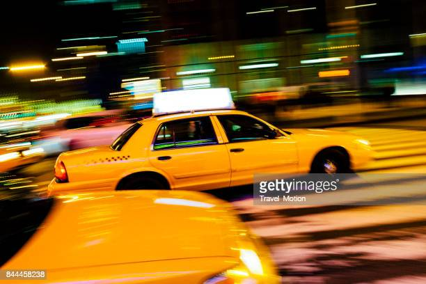 Yellow cab with panning motion at night in Manhattan