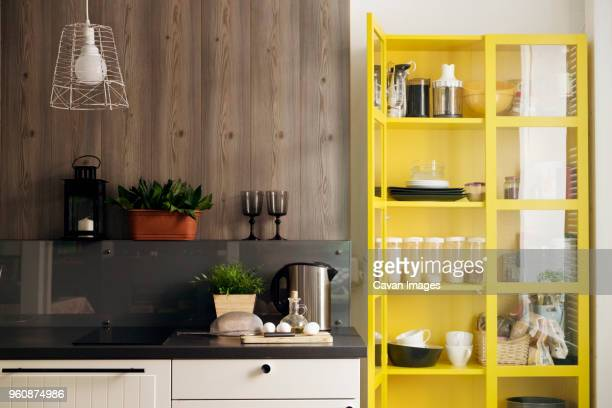 yellow cabinet by kitchen counter at home - amarillo color fotografías e imágenes de stock