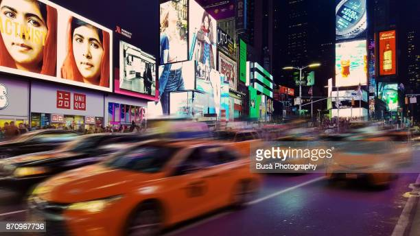 Yellow cabs driving along 7th Avenue in Times Square, Midtown Manhattan, New York City
