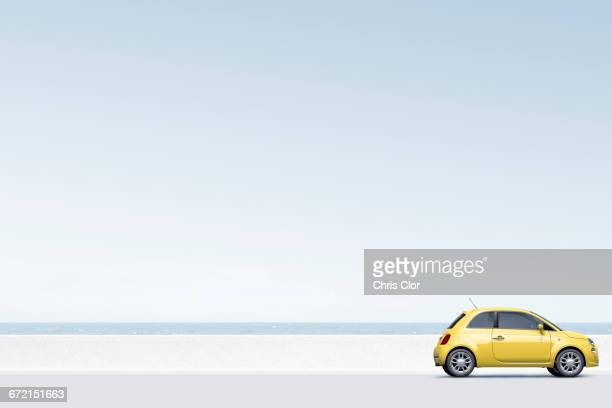 yellow car near ocean - van de zijkant stockfoto's en -beelden
