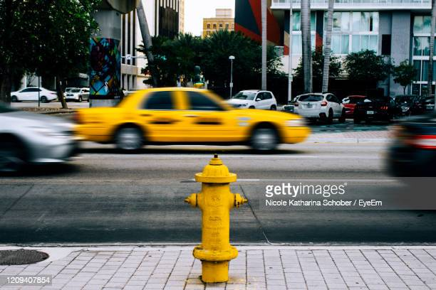yellow car on city street - fire hydrant stock pictures, royalty-free photos & images