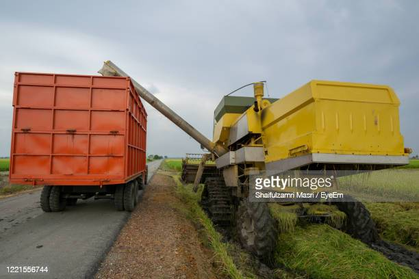 yellow cart on road amidst field against sky - shaifulzamri stock pictures, royalty-free photos & images