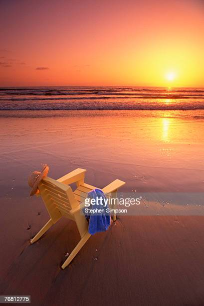 Yellow chair on beach at sunset