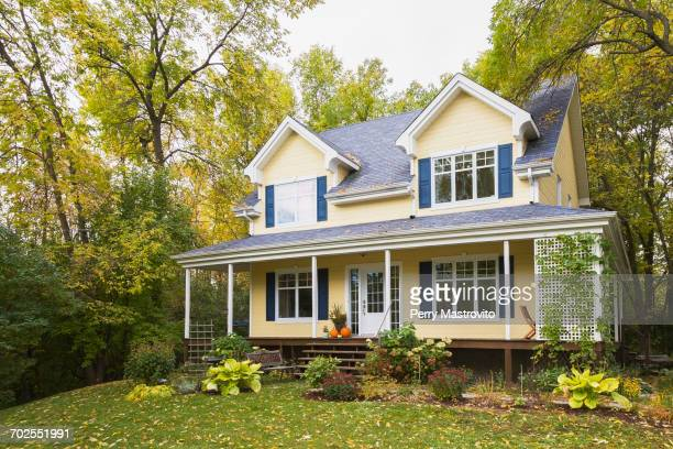 yellow clapboard with blue and white trim cottage style home facade in autumn, quebec, canada - tradition stock pictures, royalty-free photos & images