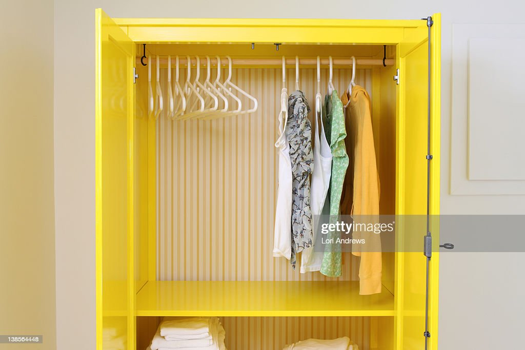 Yellow closet with doors open and hangers : ストックフォト