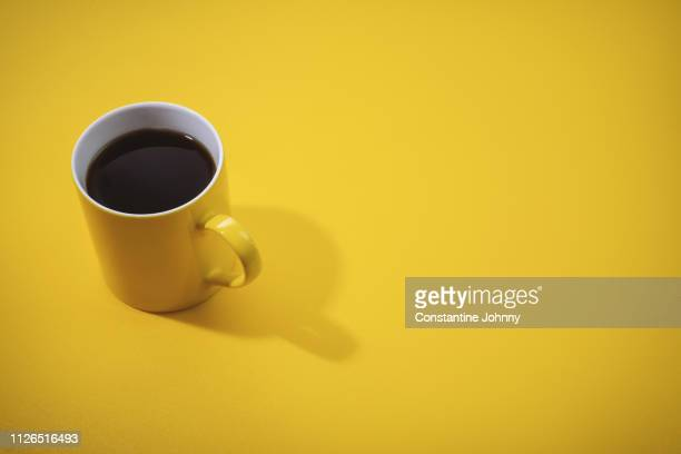yellow coffee mug on yellow background. - coffee break stock pictures, royalty-free photos & images