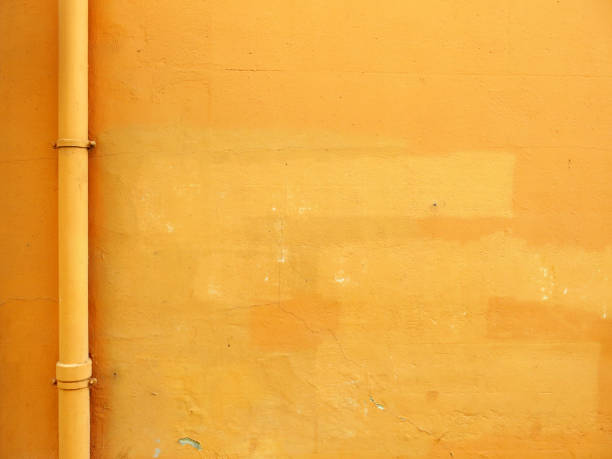 Yellow concrete wall with patina and pipe in Evian-Les-Bains