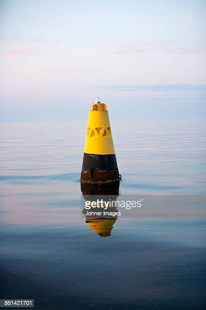 yellow cone at sea - buoy stock photos and pictures
