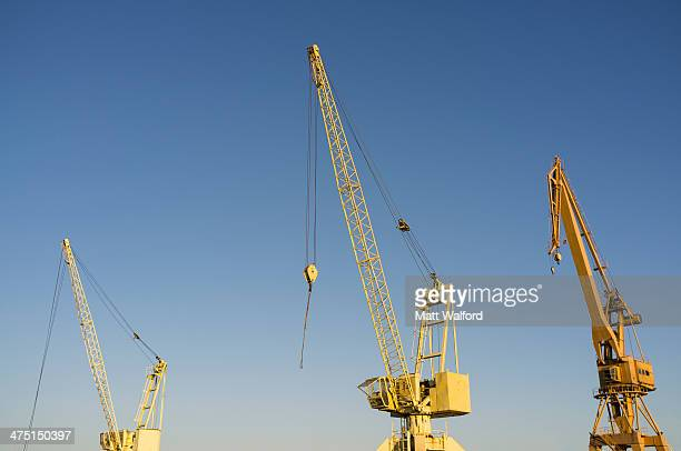 Yellow construction cranes in a row