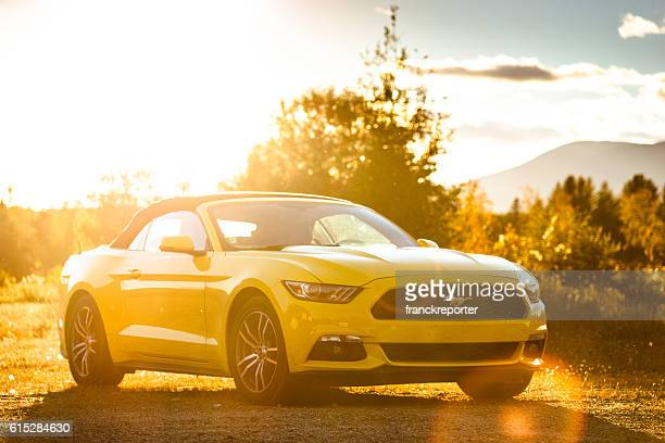 yellow convertible mustang parked at dusk - ford mustang stock photos and pictures