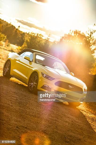 Yellow convertible mustang parked at dusk