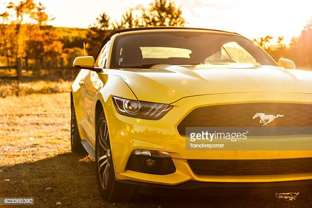 Yellow convertible mustang parked at dusk