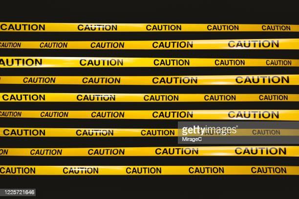yellow cordon tape with caution sign - バリアーテープ ストックフォトと画像