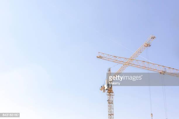 yellow crane in blue sky - munich, bavaria, germany - baumaschine stock-fotos und bilder