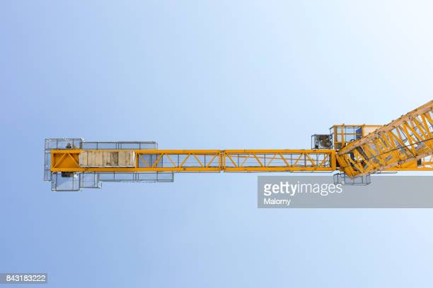 yellow crane in blue sky - munich, bavaria, germany - kran stock-fotos und bilder