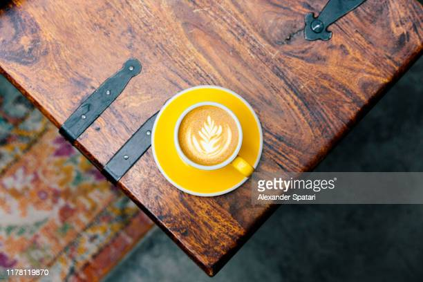 yellow cup of coffee on the table corner, high angle view - cappuccino stock pictures, royalty-free photos & images