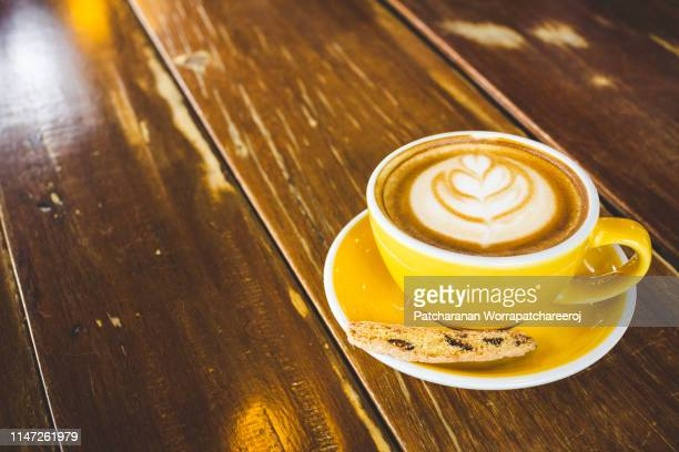 A yellow cup of hot latte art coffee on wooden table at cafe.