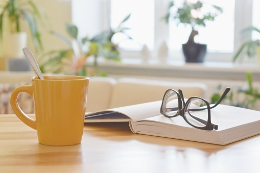Yellow cup of tea, book and glasses on the table, cozy home interior background 1135791694