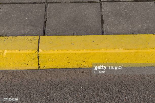 yellow curb stone border and asphalt road - curb stock pictures, royalty-free photos & images