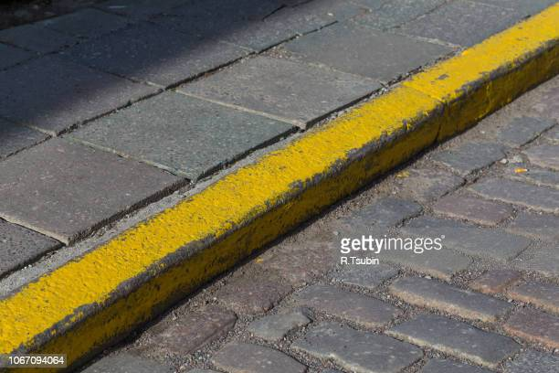 yellow curb stone border in an old town road - curb stock pictures, royalty-free photos & images