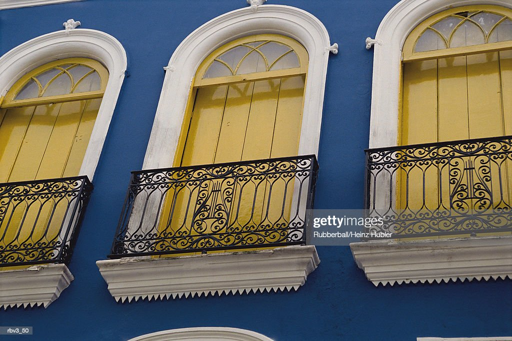 yellow curtains hang from white framed and arched windows on a blue home or building : Foto de stock