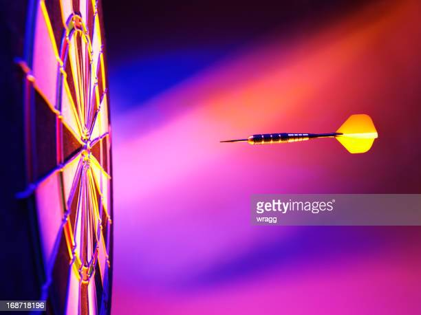 yellow dart pink lighting on a dartboard - darts stock photos and pictures