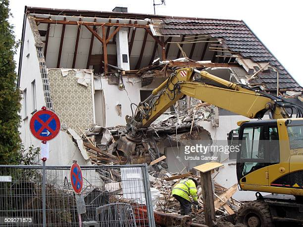 Yellow digger demolishing a home in the city