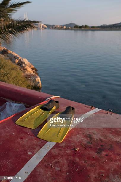 yellow diving flippers on red sailboat at dawn. - emreturanphoto stock-fotos und bilder