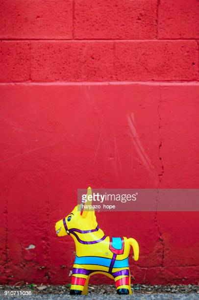Yellow donkey toy and a red wall.