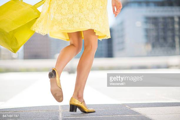 Yellow dressed woman with golden shoes and shopping bag