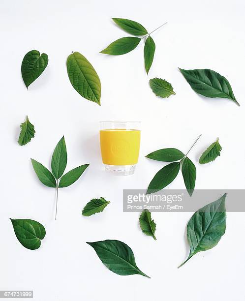 Yellow Drink Amidst Leaves Against White Background