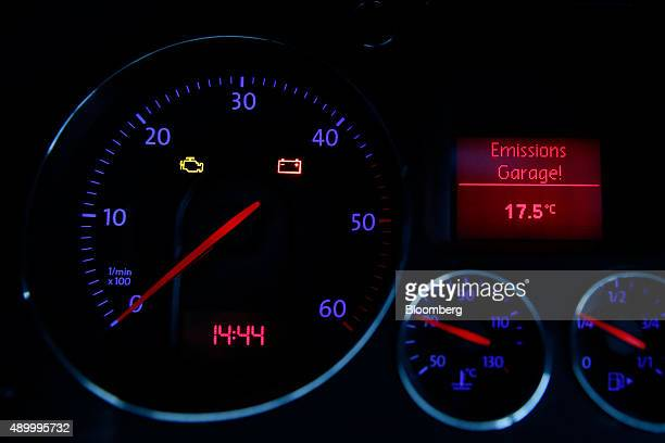 A yellow engine emissions warning icon is seen displayed on the dashboard of a Volkswagen AG Passat automobile as the vehicle sits in London UK on...