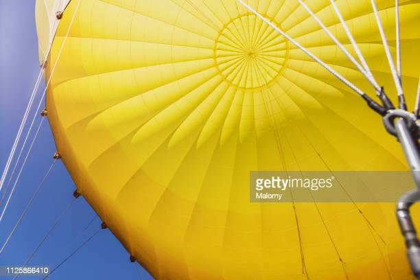 yellow envelope of a hot air balloon against clear blue sky. - beverly hills stock pictures, royalty-free photos & images