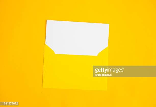 yellow envelope with white blank sheet of paper over yellow background, top view. - greeting card stock pictures, royalty-free photos & images