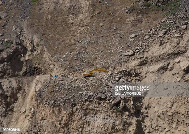 Yellow excavator working on amountain road, Badakhshan province, Darmadar, Afghanistan.