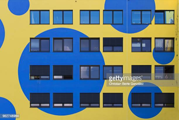yellow facade with blue circles - christian beirle stock pictures, royalty-free photos & images