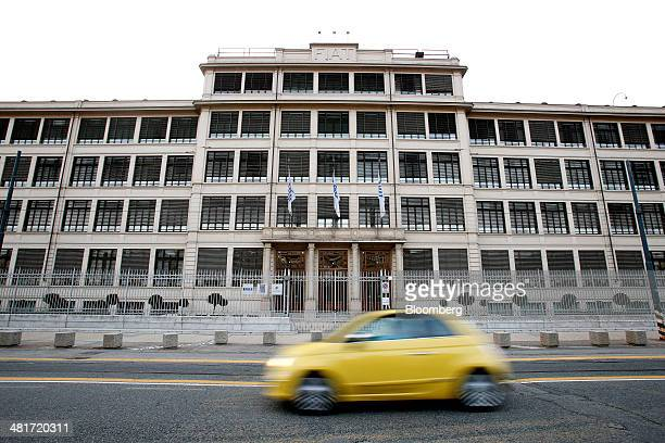 A yellow Fiat 500 automobile produced by Fiat SpA drives past the company's headquarters in Turin Italy on Sunday March 30 2014 Fiat is sticking to...