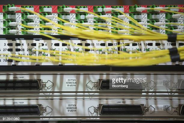 Yellow fiber optic cables sit inside a very high bit rate digital subscriber line telecoms cabinet as Royal KPN NV hold a fourth quarter earnings...