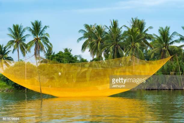 Yellow fishing net and coconut trees at beautiful countryside Cua Dai Beach