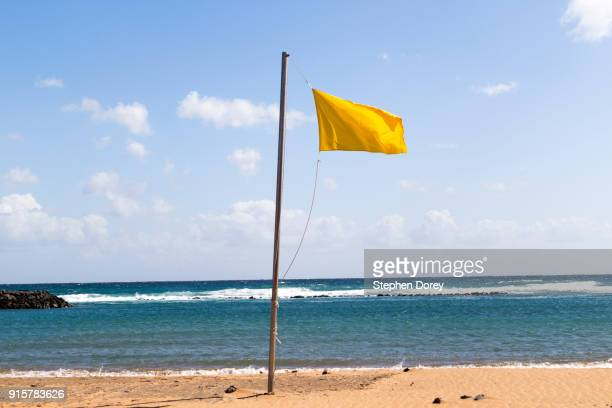 A yellow flag flying on the beach on the Canary Island of Fuerteventura